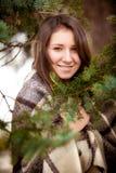 Retrato de la mujer en tela escocesa detrás del árbol de abeto Fotografía de archivo