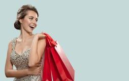 Retrato de la mujer encantadora feliz que sostiene bolsos que hacen compras rojos azul imagenes de archivo