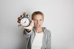 Retrato de la mujer enojada que celebra el reloj de la alarma Backgroung blanco Fotos de archivo libres de regalías