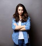 Retrato de la mujer enojada que se coloca con los brazos doblados Imágenes de archivo libres de regalías