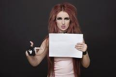 Retrato de la mujer enrrollada joven arrogante que señala hacia cartel en blanco contra fondo negro Fotos de archivo libres de regalías