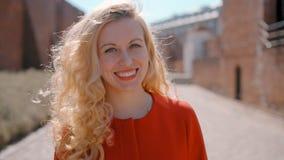 Retrato de la mujer europea rubia acertada atractiva joven que mira a la cámara almacen de metraje de vídeo
