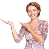 Retrato de la mujer feliz adulta con gesto de la presentación Imagenes de archivo