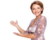Retrato de la mujer feliz adulta con gesto de la presentación Foto de archivo libre de regalías