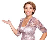 Retrato de la mujer feliz adulta con gesto de la presentación Imagen de archivo libre de regalías