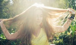 Retrato de la mujer feliz con la mano en pelo contra Imagen de archivo libre de regalías