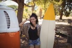 Retrato de la mujer feliz con la tabla hawaiana en furgoneta Fotos de archivo libres de regalías