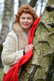 Retrato de la mujer feliz con una bufanda roja sobre un abedul Fotos de archivo libres de regalías
