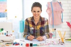 Retrato de la mujer feliz de la modista en el trabajo imagen de archivo