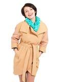 Retrato de la mujer feliz en capa beige con la bufanda verde Foto de archivo libre de regalías