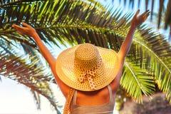 Retrato de la mujer feliz en manos de elevación del sombrero debajo de la hoja de palma en yarda del hotel Vacaciones de verano foto de archivo