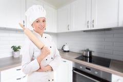 Retrato de la mujer feliz en uniforme del cocinero con rolli de madera de la hornada Fotografía de archivo