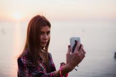 Retrato de la mujer feliz joven en la camisa del inconformista que se coloca delante de la opinión pintoresca del mar, tomando el Foto de archivo
