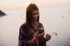 Retrato de la mujer feliz joven en la camisa del inconformista que se coloca delante de la opinión pintoresca del mar, tomando el Imagenes de archivo
