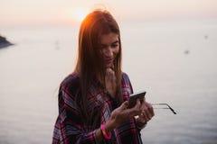 Retrato de la mujer feliz joven en la camisa del inconformista que se coloca delante de la opinión pintoresca del mar, tomando el Fotos de archivo