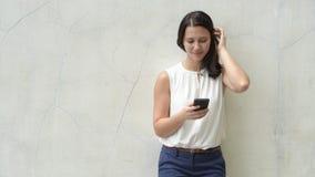 Retrato de la mujer feliz joven hermosa al aire libre usando el teléfono móvil almacen de metraje de vídeo