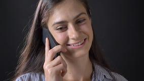 Retrato de la mujer feliz joven que habla en el teléfono y que sonríe, aislado en fondo negro almacen de metraje de vídeo