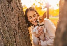 Retrato de la mujer feliz joven que sostiene el pequeño perro lindo Imagenes de archivo