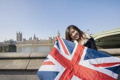 Retrato de la mujer feliz que celebra la bandera británica contra Big Ben en Londres, Inglaterra, Reino Unido Imagenes de archivo
