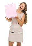 Retrato de la mujer feliz que muestra el bolso de compras rosado Imagen de archivo