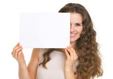 Retrato de la mujer feliz que oculta detrás del papel en blanco Fotografía de archivo