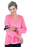 Retrato de la mujer feliz que usa reproductor Mp3 en brazal Imagen de archivo
