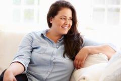 Retrato de la mujer gorda que se sienta en el sofá Fotografía de archivo