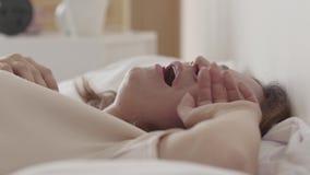 Retrato de la mujer hermosa adulta que miente en la cama que bosteza, ella no quiere levantarse el primer Se?ora atractiva metrajes
