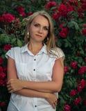 Retrato de la mujer hermosa cerca de Bush de caderas rojo oscuro Foto de archivo
