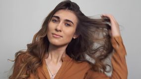 Retrato de la mujer hermosa con el pelo largo rizado en el fondo blanco Maquillaje, moda, belleza almacen de metraje de vídeo