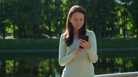 Retrato de la mujer hermosa con el smartphone que se coloca en luz del sol metrajes
