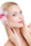 Retrato de la mujer hermosa con la flor de la orquídea en su pelo. Woman Face modelo hermoso. Piel perfecta. Make-up.Makeup profes Imagen de archivo