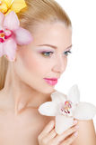 Retrato de la mujer hermosa con la flor de la orquídea en su pelo. Woman Face modelo hermoso. Piel perfecta. Make-up.Makeup profes Foto de archivo libre de regalías