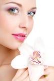 Retrato de la mujer hermosa con la flor de la orquídea en su pelo. Woman Face modelo hermoso. Piel perfecta. Make-up.Makeup profes Foto de archivo