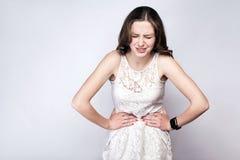 Retrato de la mujer hermosa con las pecas y vestido del blanco y reloj elegante con dolor de estómago en fondo de los gris platea Fotos de archivo libres de regalías