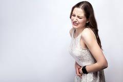 Retrato de la mujer hermosa con las pecas y vestido del blanco y reloj elegante con dolor de estómago en fondo de los gris platea imágenes de archivo libres de regalías