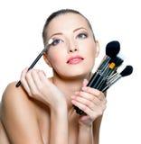 Retrato de la mujer hermosa con los cepillos del maquillaje Foto de archivo