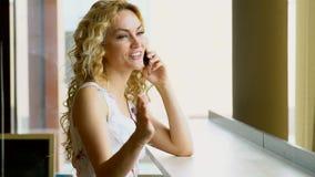Retrato de la mujer hermosa con sonrisa de emisión que habla en el teléfono en café almacen de video
