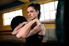 Retrato de la mujer hermosa del ajuste mientras que hace ejercicio duro en el gimnasio Imagen de archivo libre de regalías