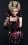 Retrato de la mujer hermosa del diablo en vestido sexy oscuro Imagen de archivo libre de regalías