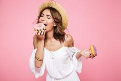 Retrato de la mujer hermosa en el sombrero blanco del vestido y de paja, comiendo Fotografía de archivo