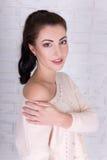 Retrato de la mujer hermosa en el suéter blanco sobre el wa blanco del ladrillo Fotografía de archivo