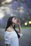 Retrato de la mujer hermosa en el vestido blanco que se coloca en la calle rodeada por los árboles púrpuras del Jacaranda Imagen de archivo libre de regalías