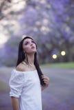 Retrato de la mujer hermosa en el vestido blanco que se coloca en la calle rodeada por los árboles púrpuras del Jacaranda Imágenes de archivo libres de regalías