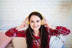Retrato de la mujer hermosa en la música que escucha de la mañana que se sienta en cama en casa Fotos de archivo libres de regalías