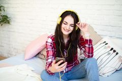 Retrato de la mujer hermosa en la música que escucha de la mañana que se sienta en cama en casa fotografía de archivo libre de regalías