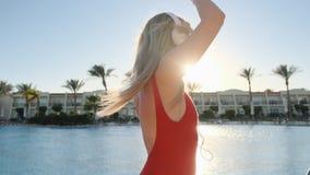 Retrato de la mujer hermosa en traje de baño rojo y de la música de los auriculares, del baile y el escuchar en smartphone usando almacen de metraje de vídeo
