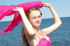 Retrato de la mujer hermosa en traje de baño rosado con la bufanda en el b Imagenes de archivo