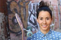 Retrato de la mujer hermosa feliz con el pelo largo en una camisa y sostener del dril de algodón del bollo que lleva su monopatín Fotografía de archivo libre de regalías