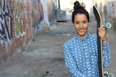 Retrato de la mujer hermosa feliz con el pelo largo en una camisa y sostener del dril de algodón del bollo que lleva su monopatín Imagen de archivo